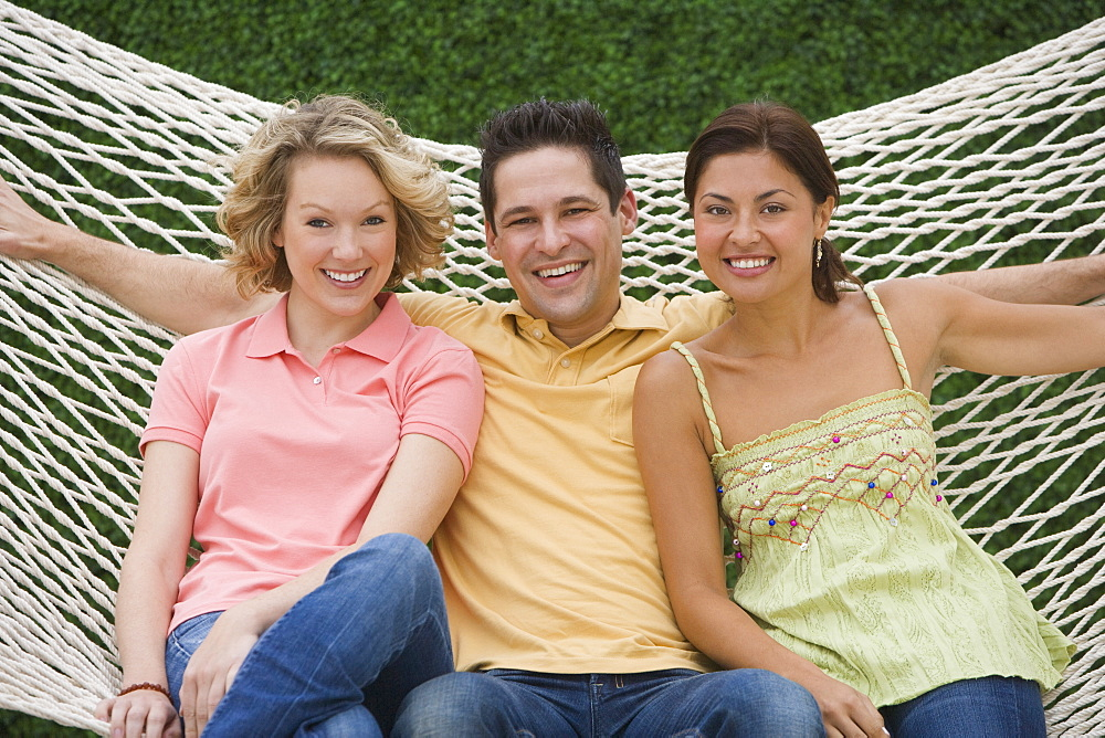 Multi-ethnic friends sitting on hammock