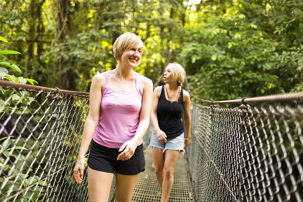 Young women walking on footbridge in forest, Costa Rica