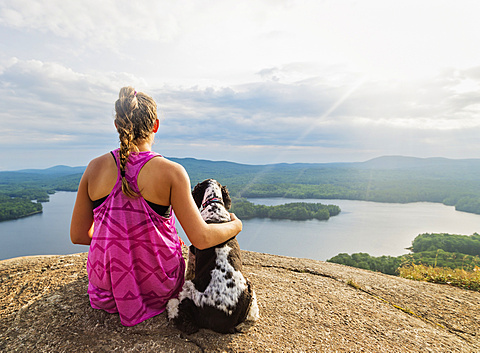 Young woman sitting with dog on cliff looking at lake view, USA, Maine, Camden