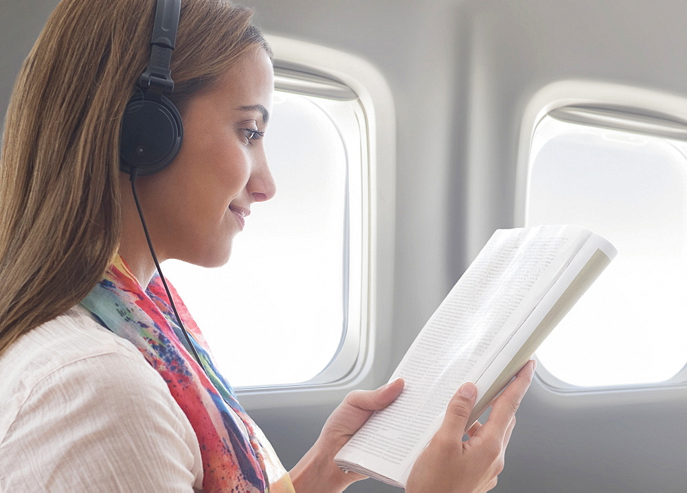 Young woman wearing headphones while reading book on plane