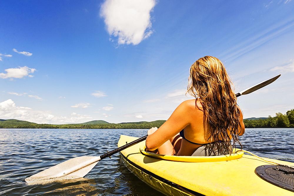Young woman kayaking on lake