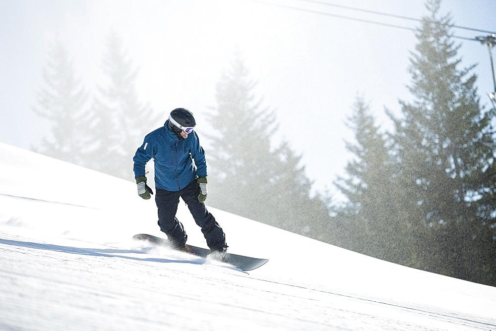 Man snowboarding downhill, USA, Montana, Whitefish