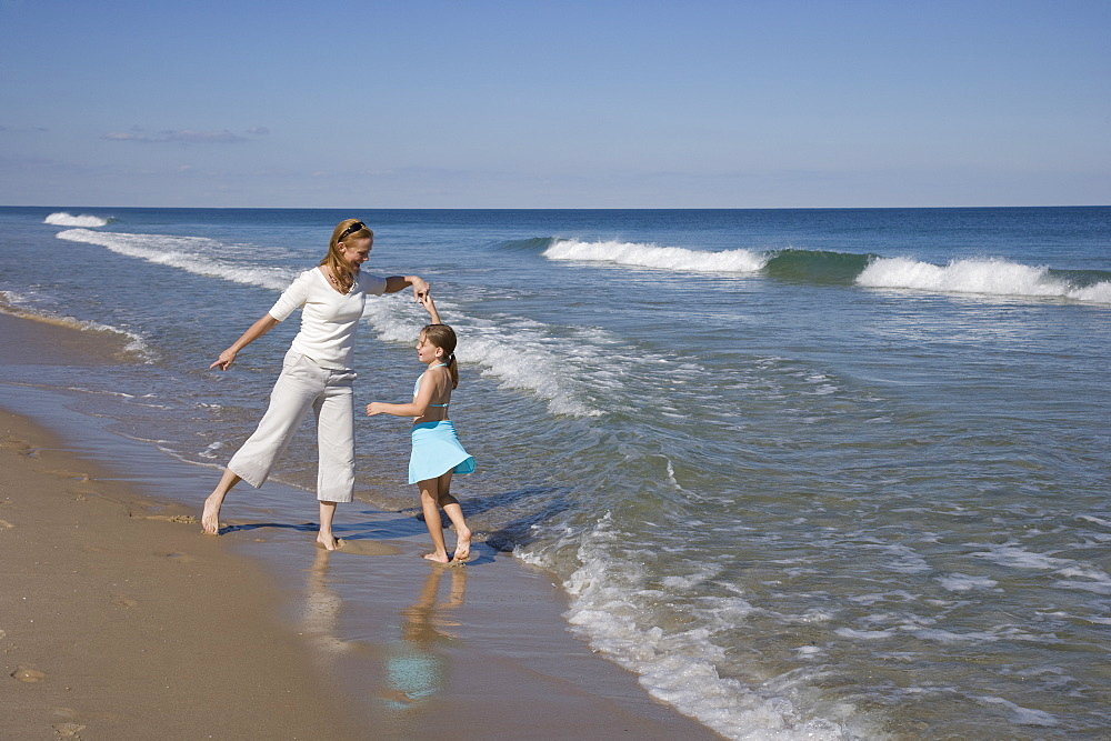 Mother and daughter dancing at beach