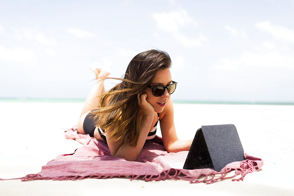 Woman with tablet on tropical beach