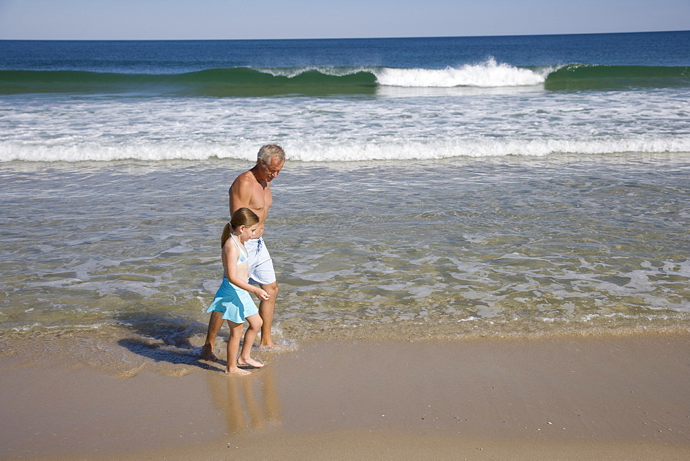 Father and daughter walking in ocean surf