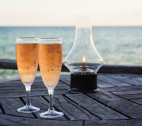 Wineglasses and oil lamp on table with sea in background