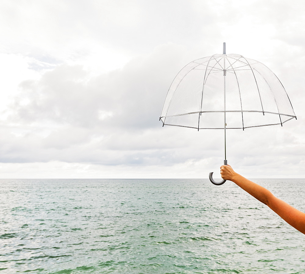 Person holding umbrella against cloudy sky
