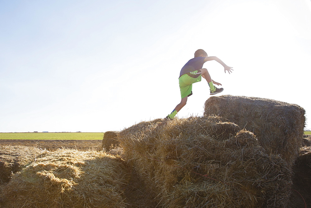 Boy (6-7) jumping on bale of hay
