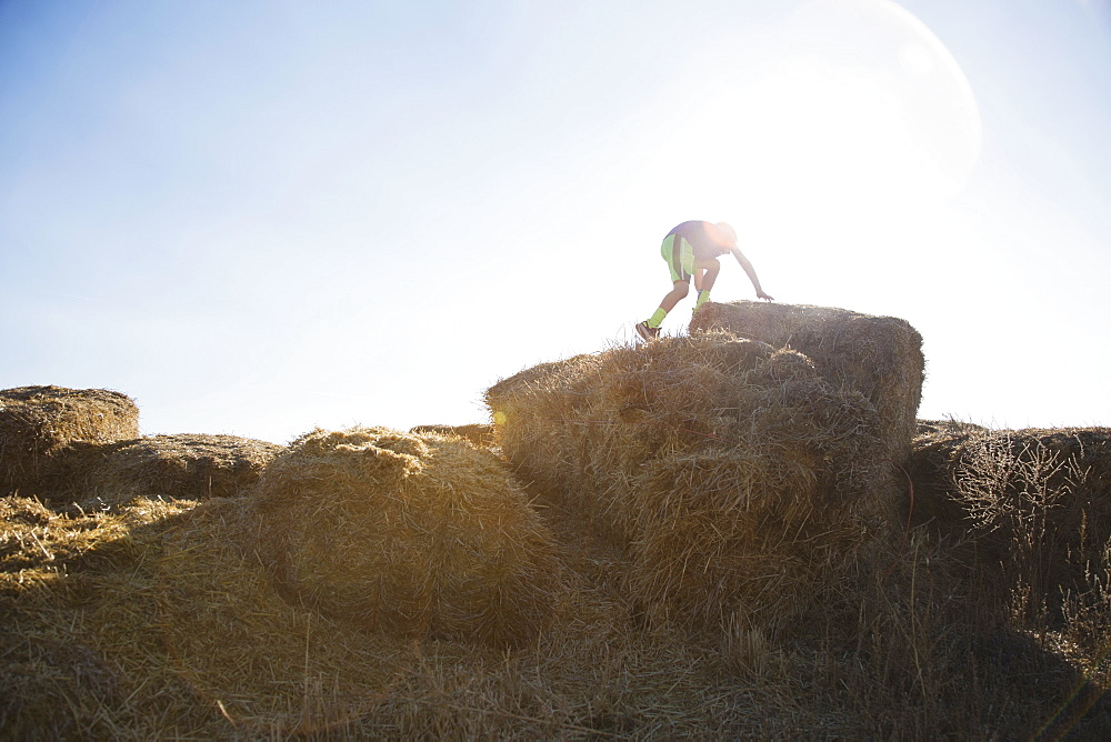 Boy (6-7) climbing on bale of hay