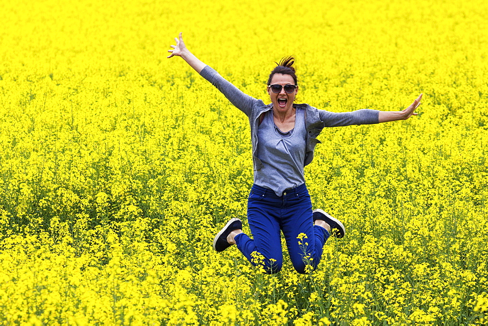 Italy, Tuscany, Woman jumping in canola field