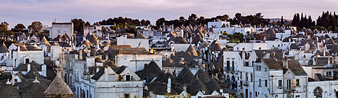 Italy, Apulia, Alberobello, Old town panorama of old trulli houses at sunset