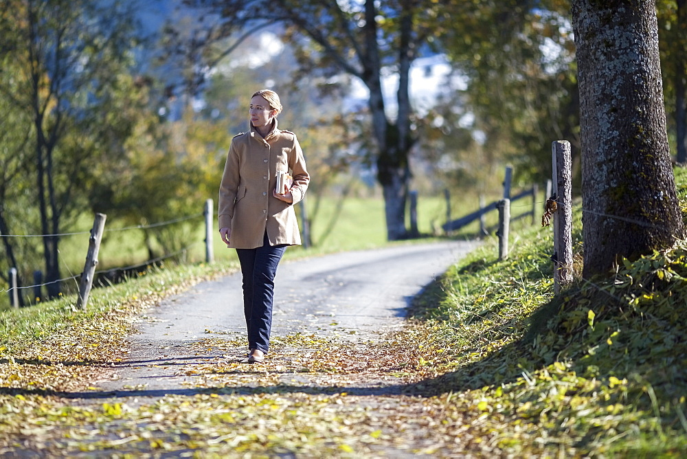 Austria, Salzburger Land, Maria Alm, Mature woman walking on autumn alley