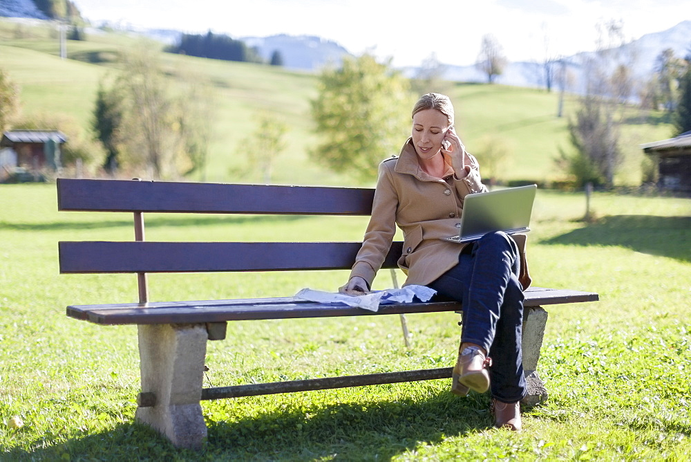 Austria, Salzburger Land, Maria Alm, Mature woman sitting on bench and talking on phone