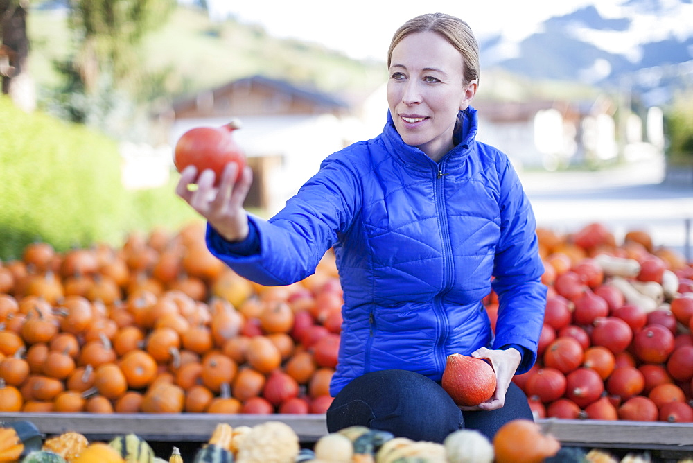 Austria, Salzburger Land, Maria Alm, Mature woman in blue jacket holding red vegetables