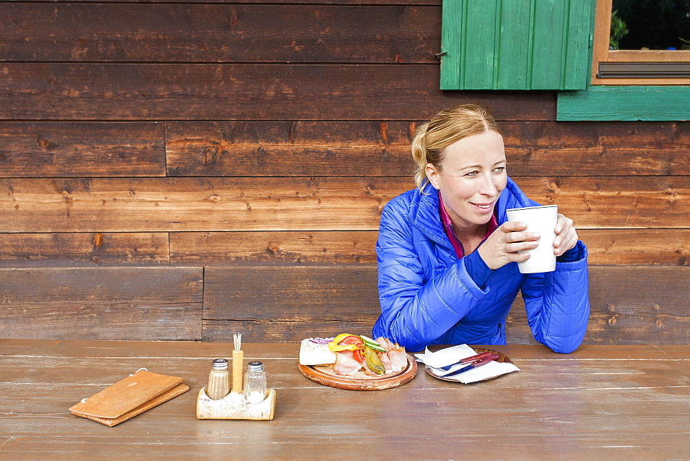 Austria, Salzburger Land, Maria Alm, Mature woman drinking coffee at wooden table