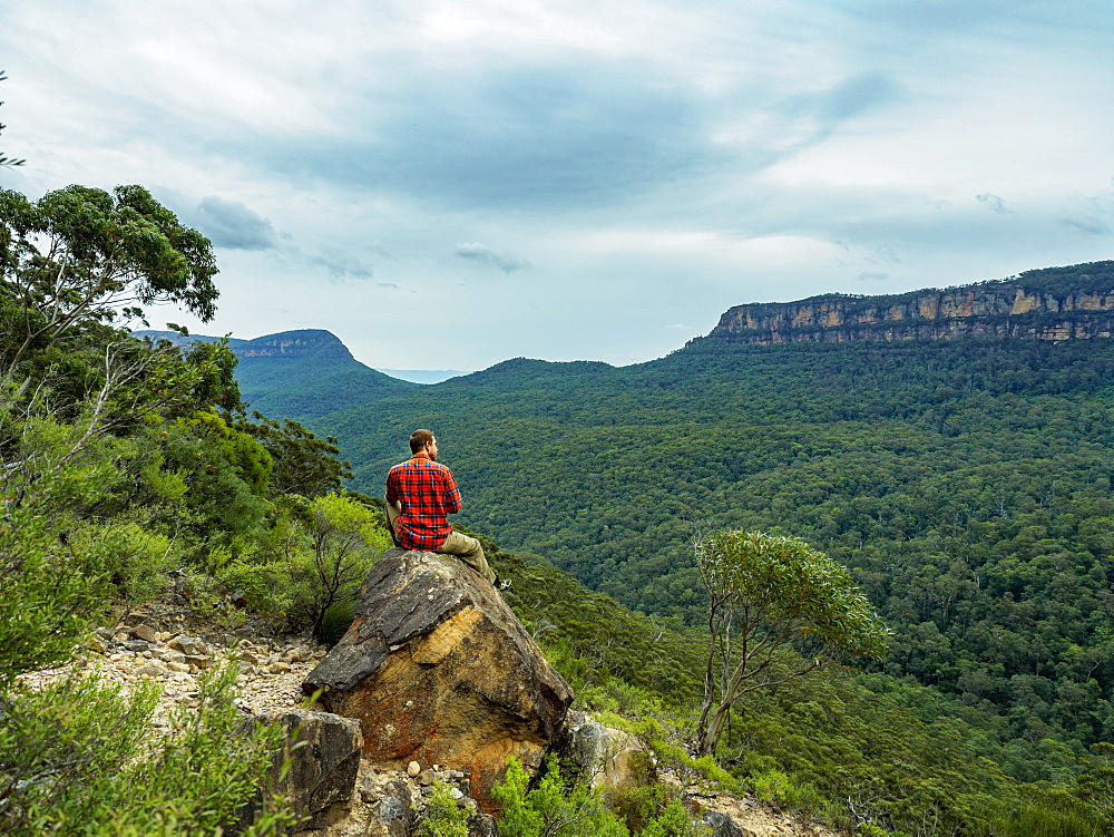 Australia, New South Wales, Katoomba, Rear view of mid adult man sitting on rock and looking at Blue Mountains