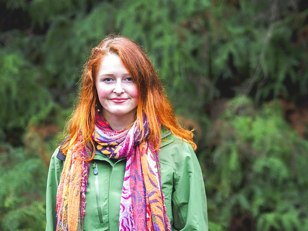 Portrait of smiling redhead in scarf and green jacket