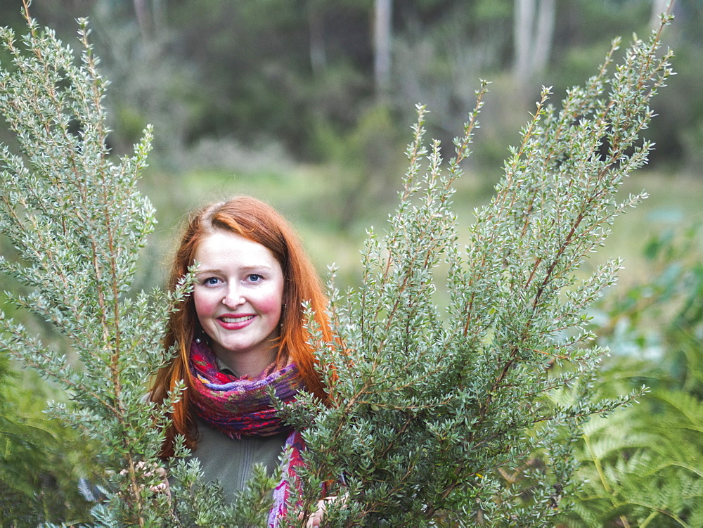 Portrait of smiling redhead in bushes
