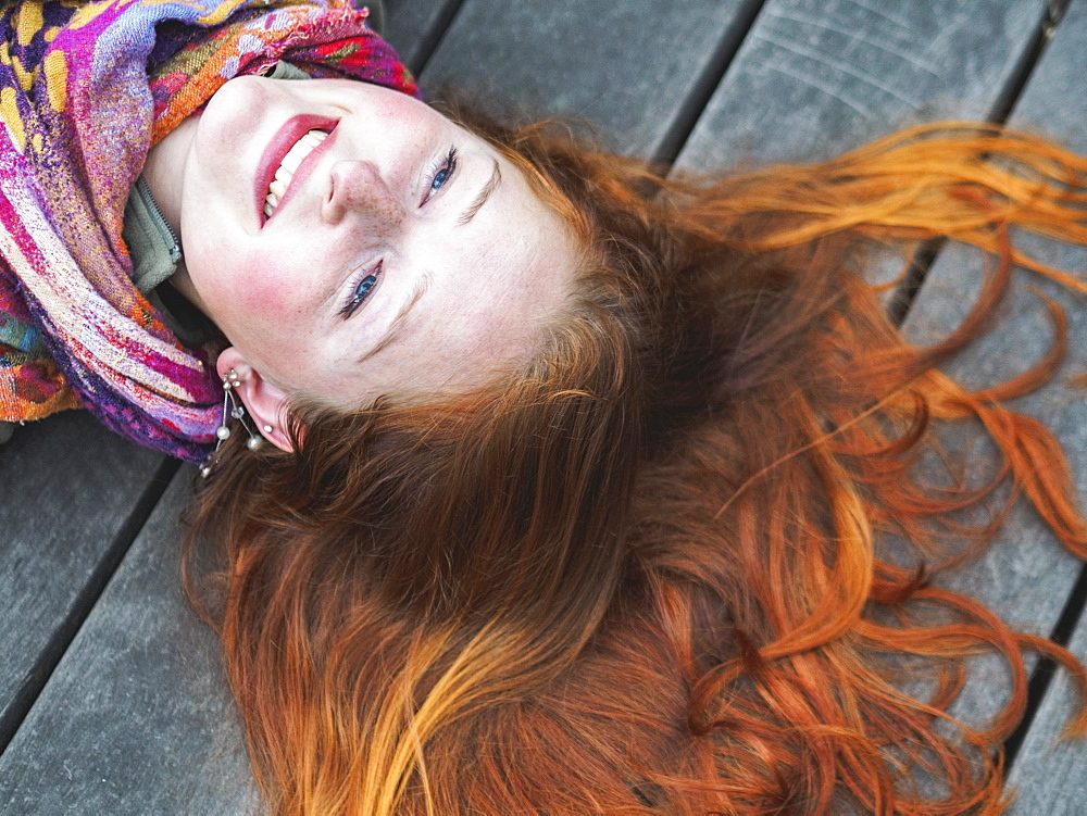 Portrait of smiling redhead lying down