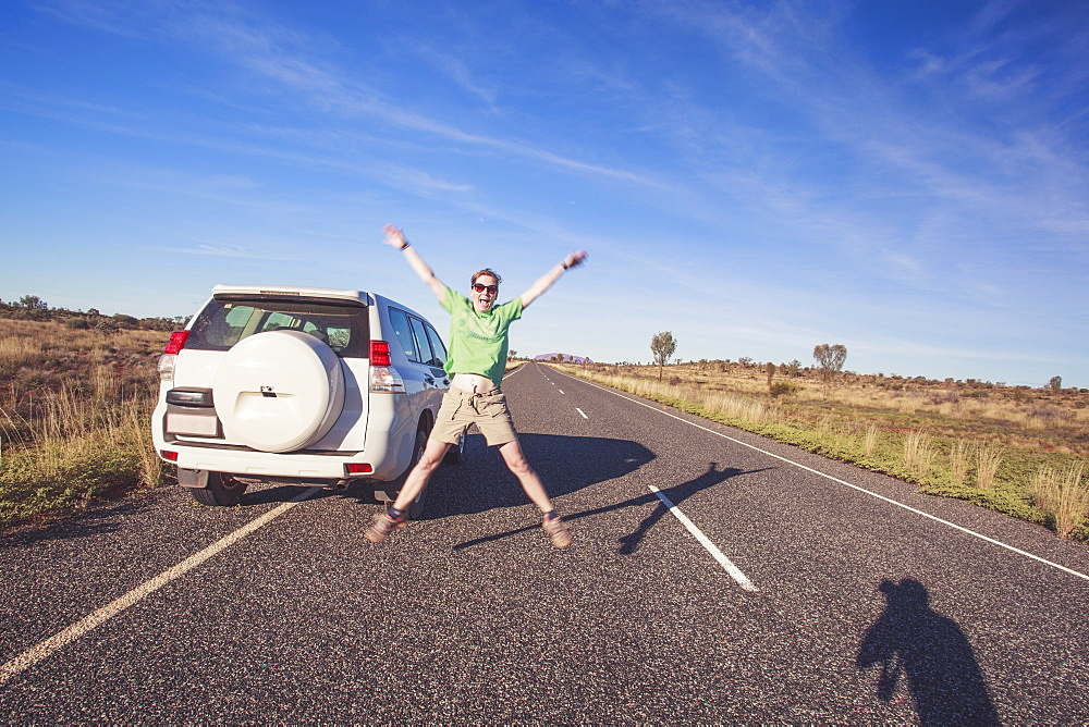 Australia, Outback, Northern Territory, Red Centre, Uluru-Kata Tjuta National Park, Woman jumping next to SUV car on road in wilderness - 1178-25790
