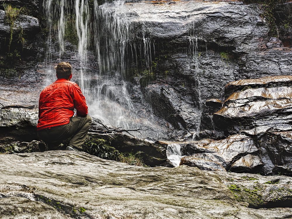 Australia, New South Wales, Blue Mountains, Mid-adult man crouching at foot of waterfall