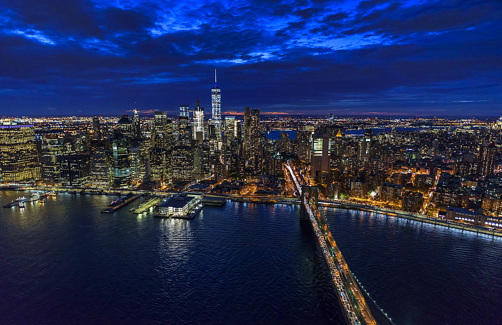 USA, New York, New York City, Manhattan, Aerial view of illuminated skyline with harbor and Brooklyn bridge at night