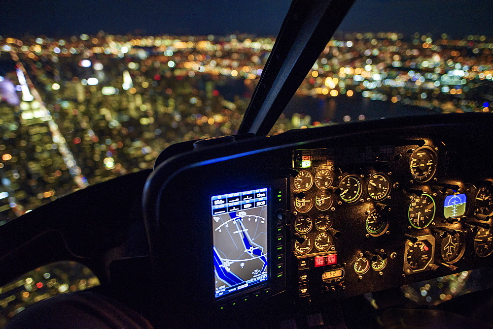 USA, New York, New York City, Illuminated skyline at night seen from helicopter cockpit