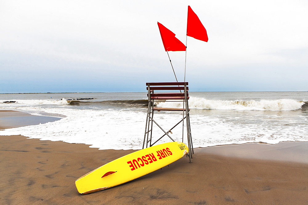 USA, New York State, New York City, Brooklyn, Yellow surfboard and empty lifeguard stand on beach