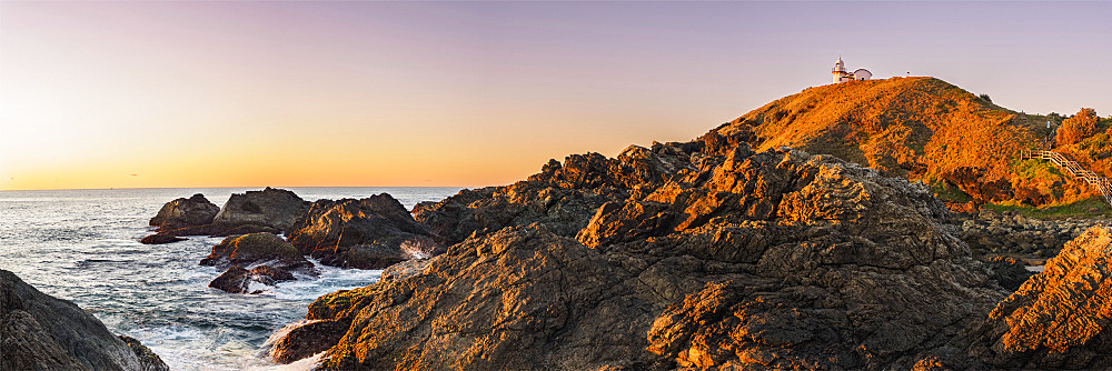 Australia, New South Wales, Port Macquarie, Lighthouse on rocky coat at sunrise