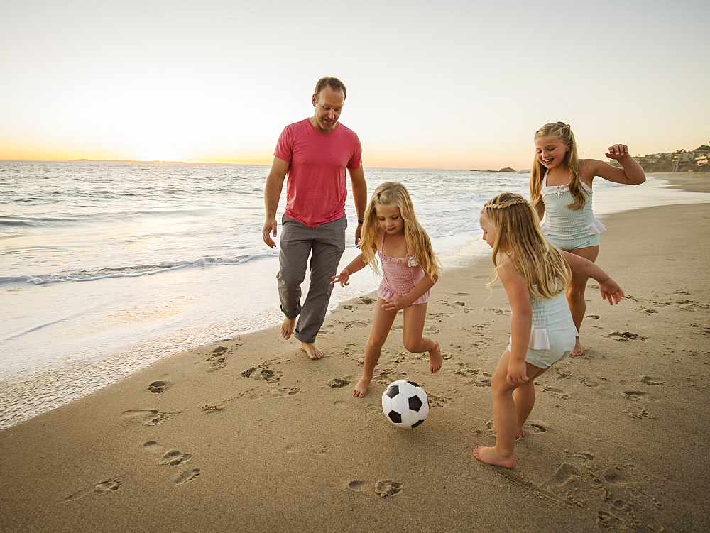 Father with children (4-5, 6-7, 8-9) playing soccer on beach - 1178-25977