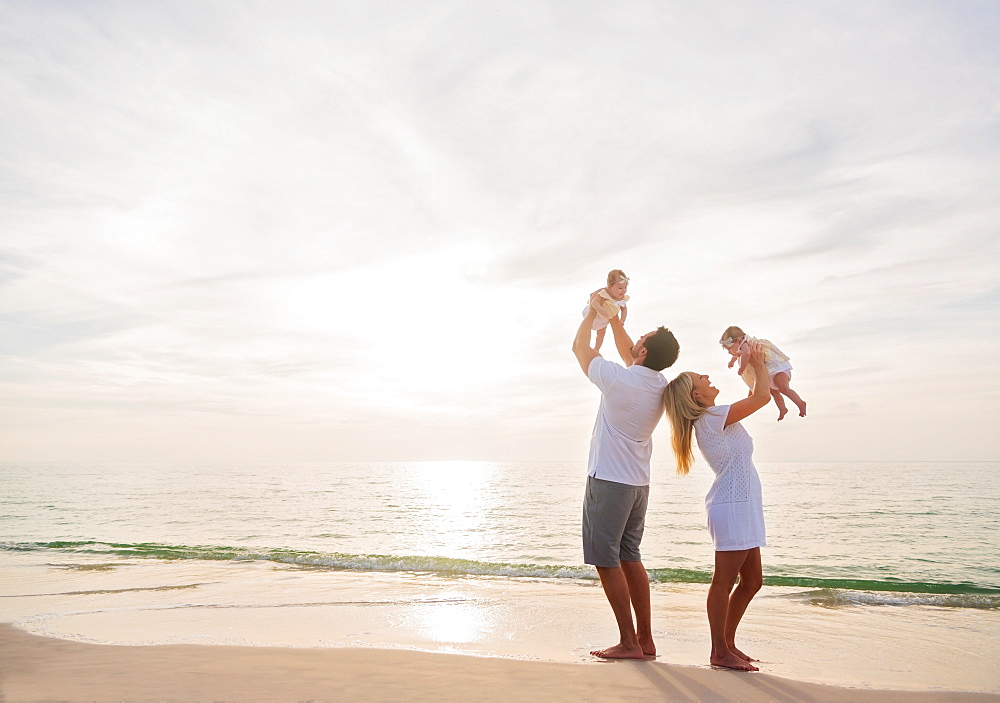 Happy family with two baby girls (2-5 months) at beach in sunlight