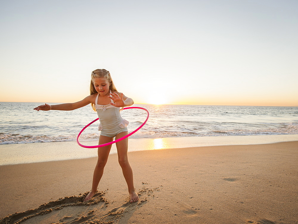 Girl (8-9) spinning plastic hoop on beach