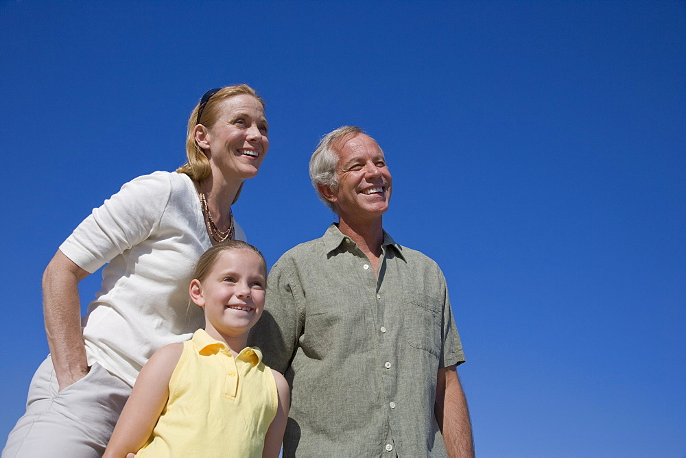 Low angle view of family under blue sky