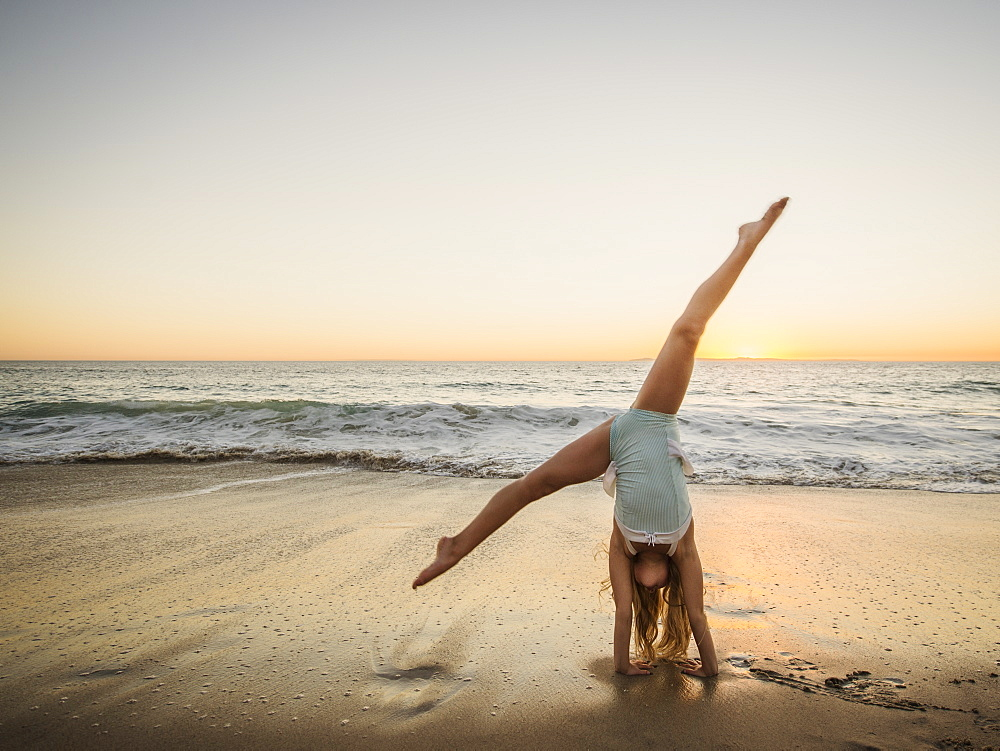Girl (8-9) doing cartwheel on beach