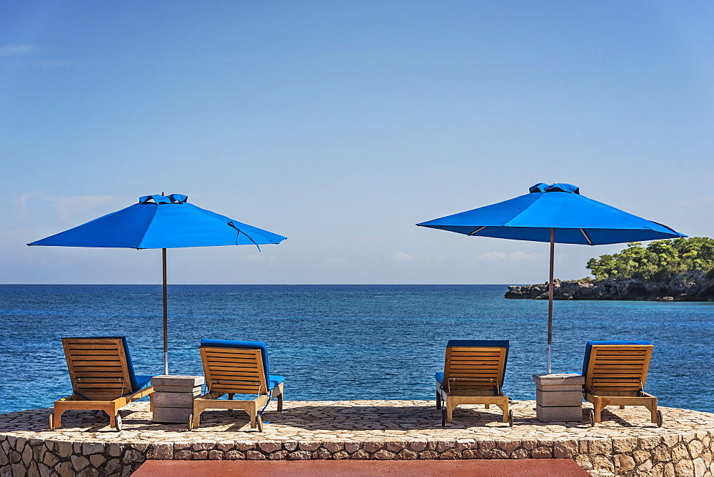 Jamaica, Negril, Beach umbrellas and lounge chairs against tranquil seascape