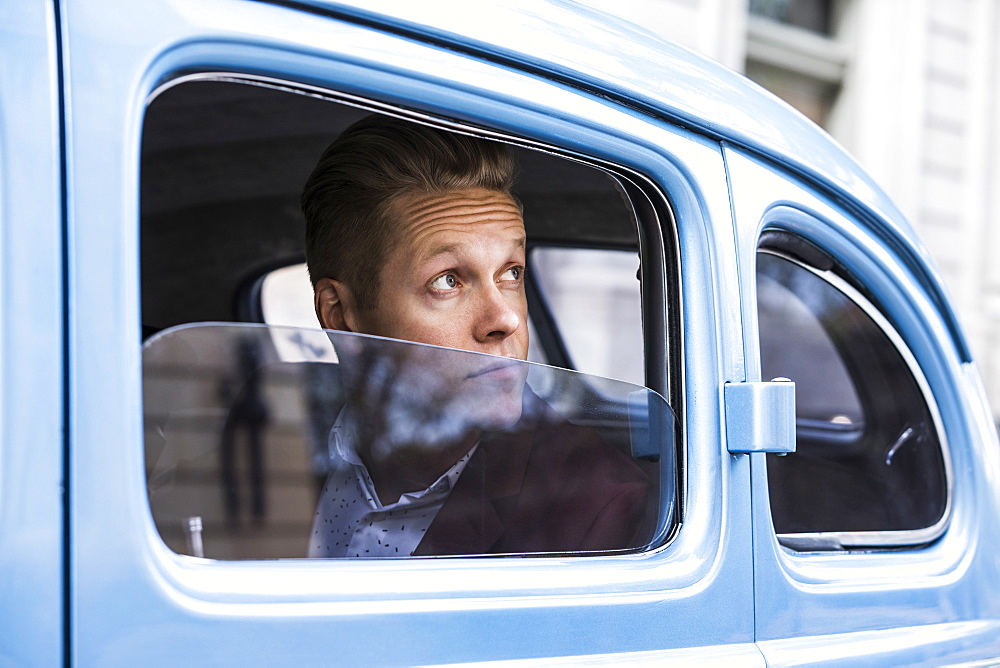 Man looking through window in retro car