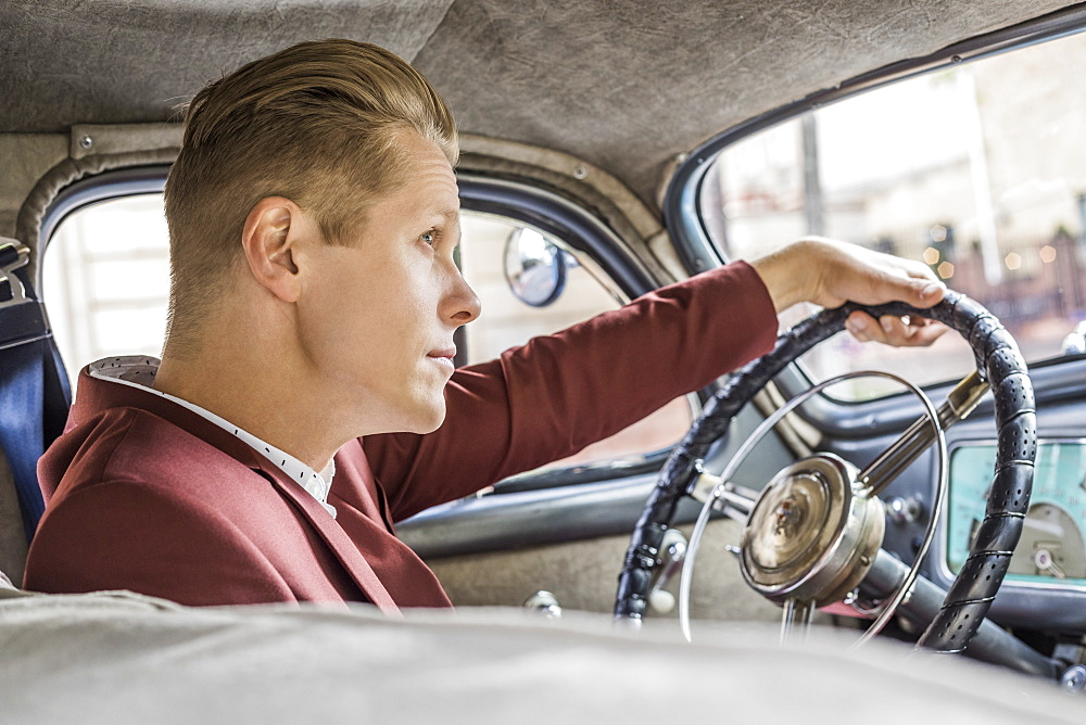 Blond man driving vintage car