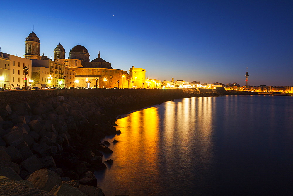 Spain, Andalusia, Cadiz, Cathedral de Cadiz and waterfront buildings at night