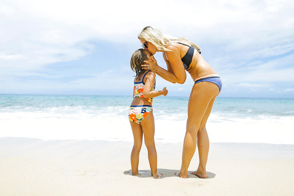 Mother kissing daughter (6-7) on beach