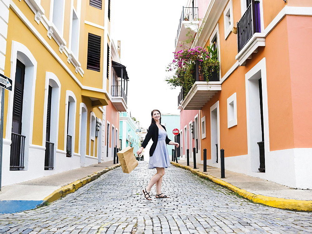 Puerto Rico, San Juan, Woman with shopping bag walking city streets