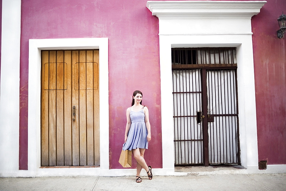 Puerto Rico, San Juan, Woman with shopping bag standing in front of pink building