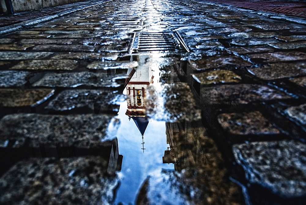 Spain, Andalusia, Seville, La Macarena, Church reflecting on wet cobblestone street