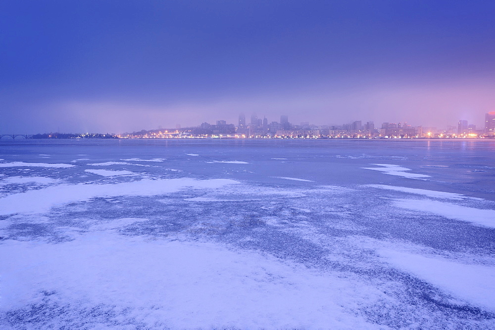 Ukraine, Dnepropetrovsk region, Dnepropetrovsk city, Dramatic sky over frozen river at dusk