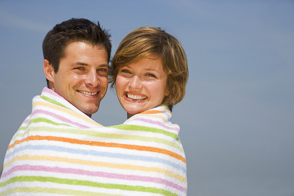 Couple wrapped in beach towel