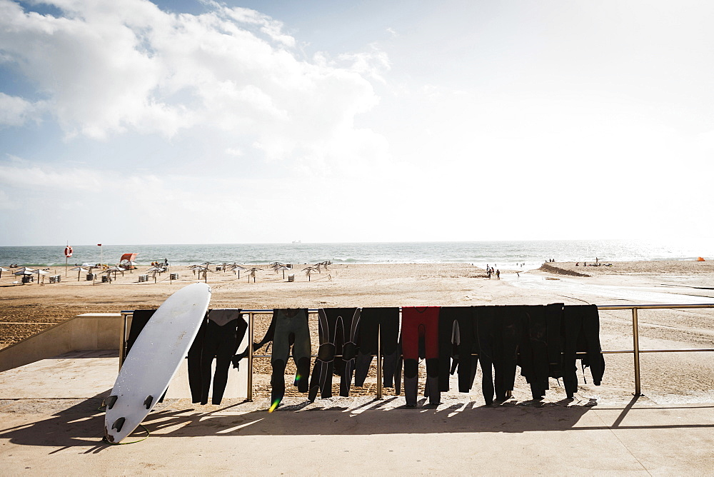 Wetsuits and surfboard on railing at Carcavelos Beach, Carcavelos, Lisbon, Portugal