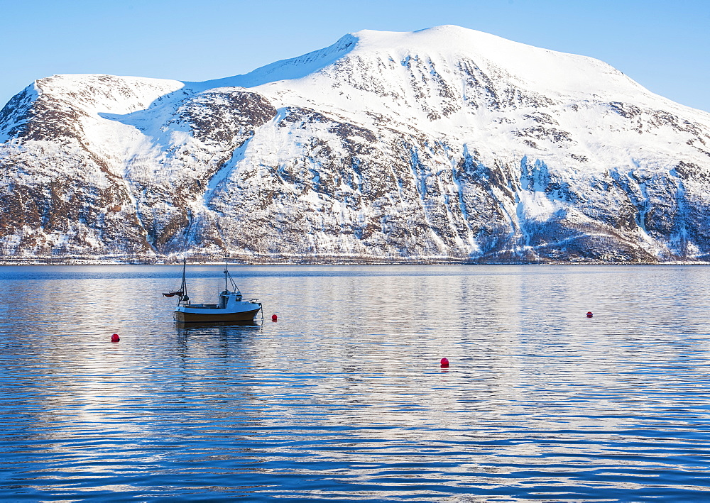 Fishing boat by snow covered mountain in Tromso, Norway