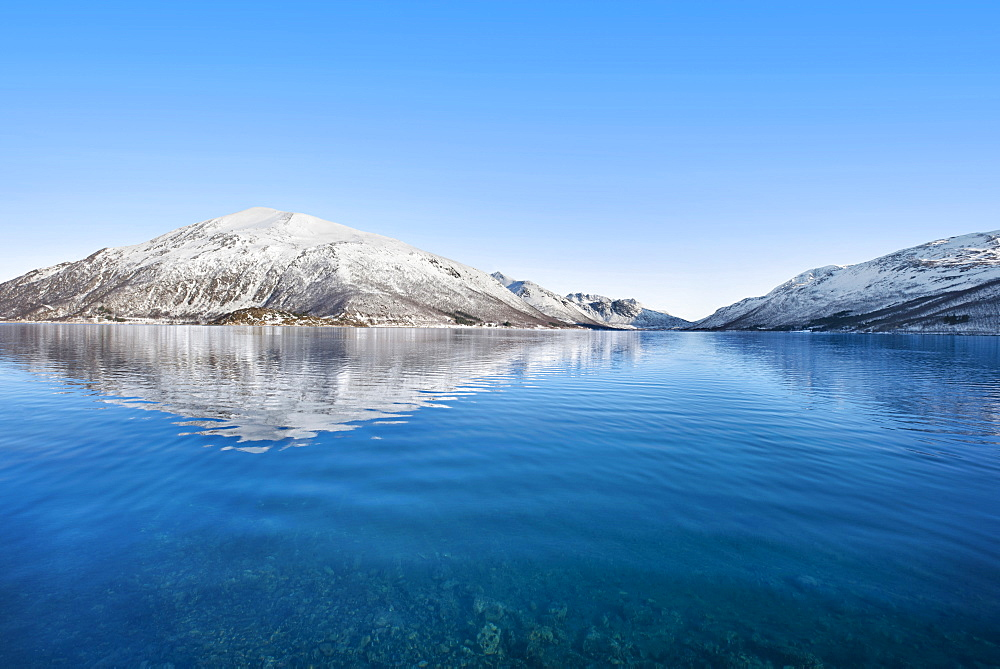Snow covered hills by sea in Tromso, Norway