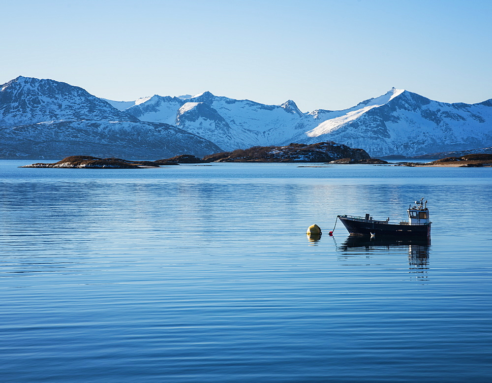 Fishing boat by snow covered mountains in Tromso, Norway