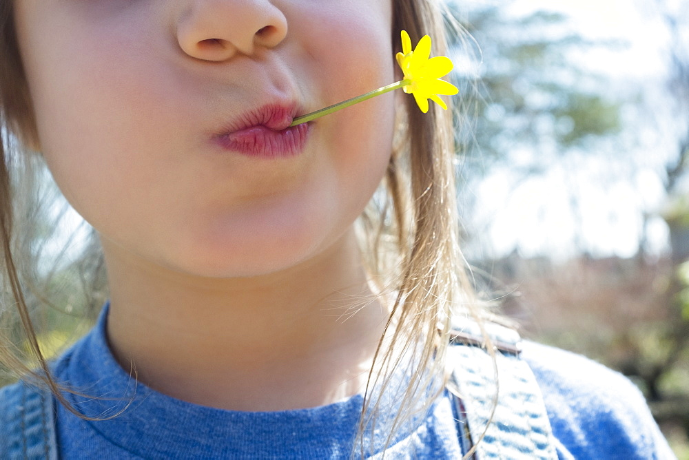 Girl with yellow flower in mouth