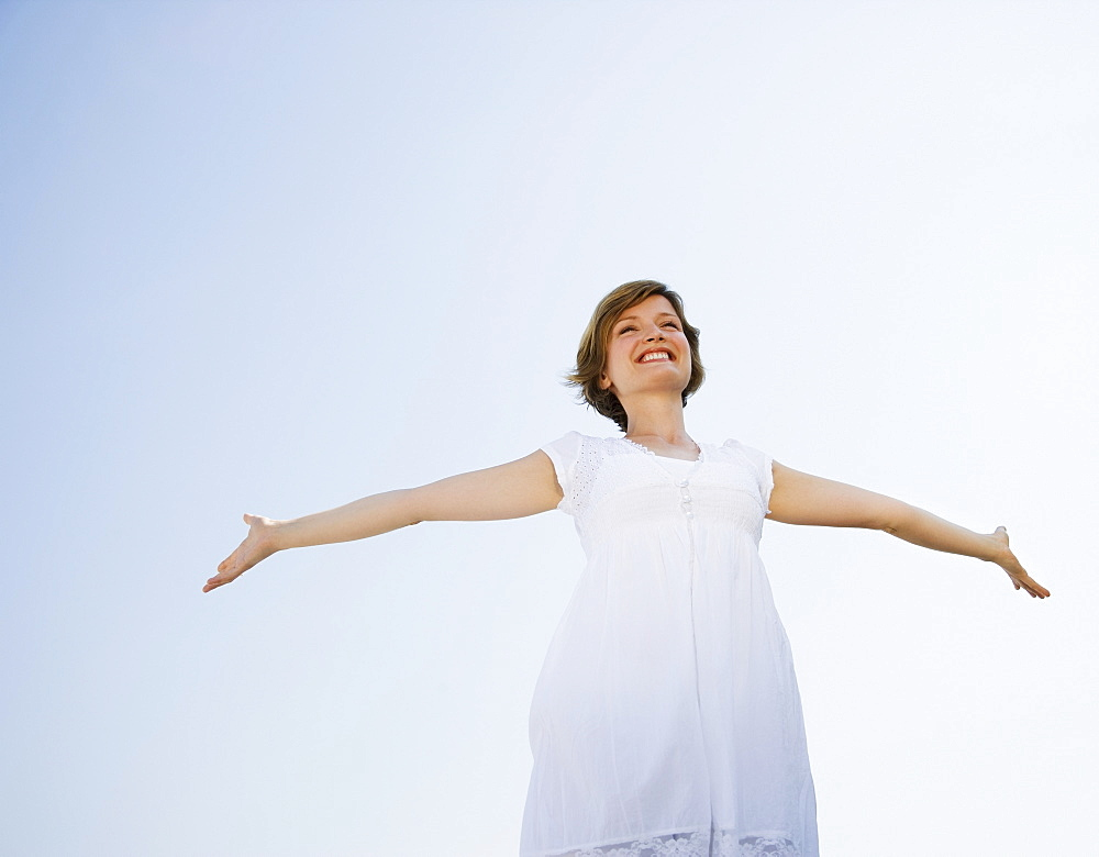 Low angle view of woman with arms outstretched